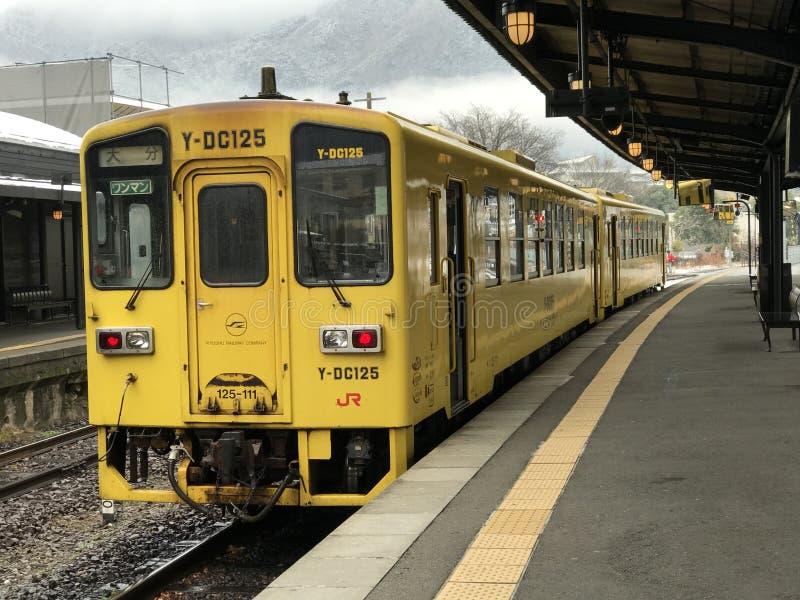 Το ιαπωνικό τοπικό τραίνο σε κίτρινο περιμένει στην πλατφόρμα στοκ φωτογραφίες
