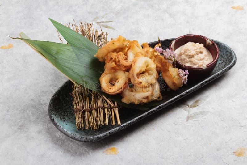 Το ιαπωνικό τσιγαρισμένο καλαμάρι που αναμιγνύει το καλαμάρι Karaage αλευριού tempura εξυπηρέτησε με τη σάλτσα στο μαύρο ιαπωνικό στοκ εικόνες με δικαίωμα ελεύθερης χρήσης