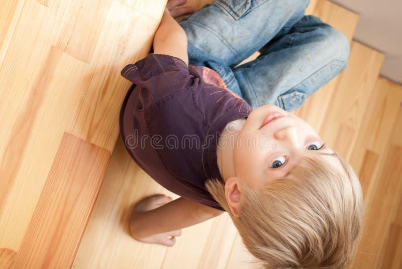 Το διασκεδάζοντας αγόρι κάθεται σε μια σκάλα στοκ εικόνα