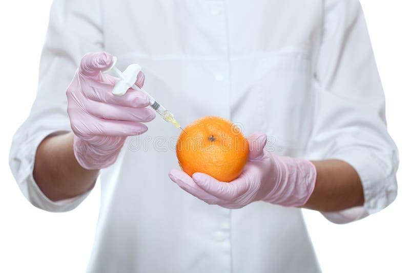 Το ιατρικό cosmetologist κρατά μια σύριγγα για την έγχυση και το πορτοκάλι στο σαλόνι ομορφιάς στοκ φωτογραφία
