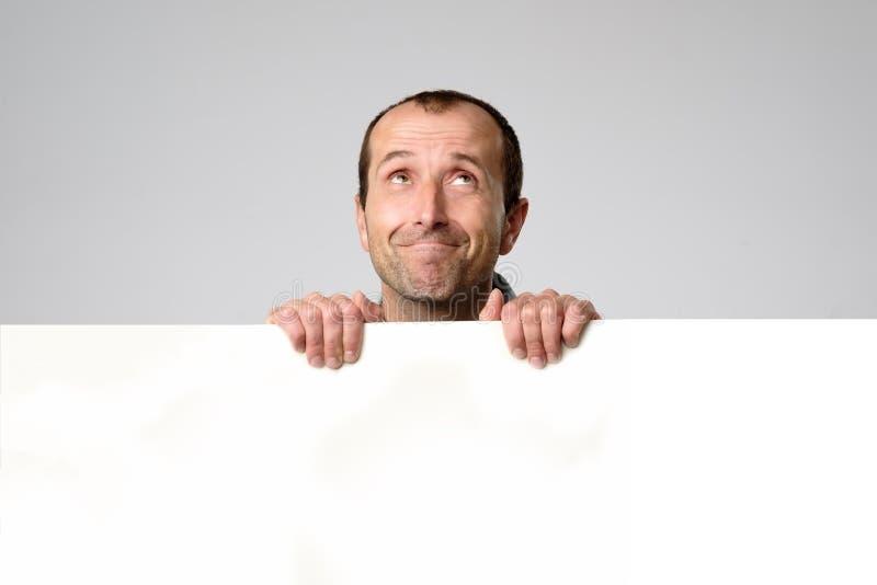 Το ισπανικό άτομο κρατά το κενό σημάδι σε ένα άσπρο υπόβαθρο στούντιο στοκ φωτογραφίες