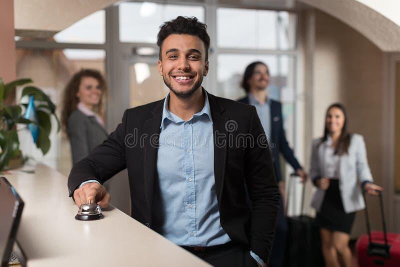Το ισπανικό επιχειρησιακό άτομο φθάνει στο ξενοδοχείο περιμένοντας τον έλεγχο στην ομάδα επιχειρηματιών εγγραφής στο λόμπι στοκ φωτογραφίες