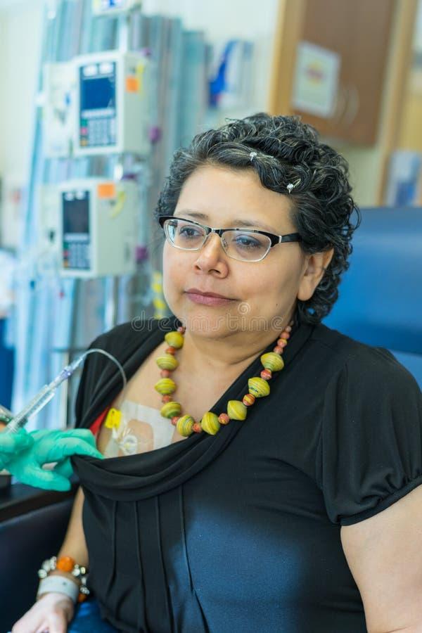 Το ισπανικό θηλυκό περιμένει Pateintly κατά τη διάρκεια της έγχυσης επεξεργασίας Chemo στοκ φωτογραφία με δικαίωμα ελεύθερης χρήσης