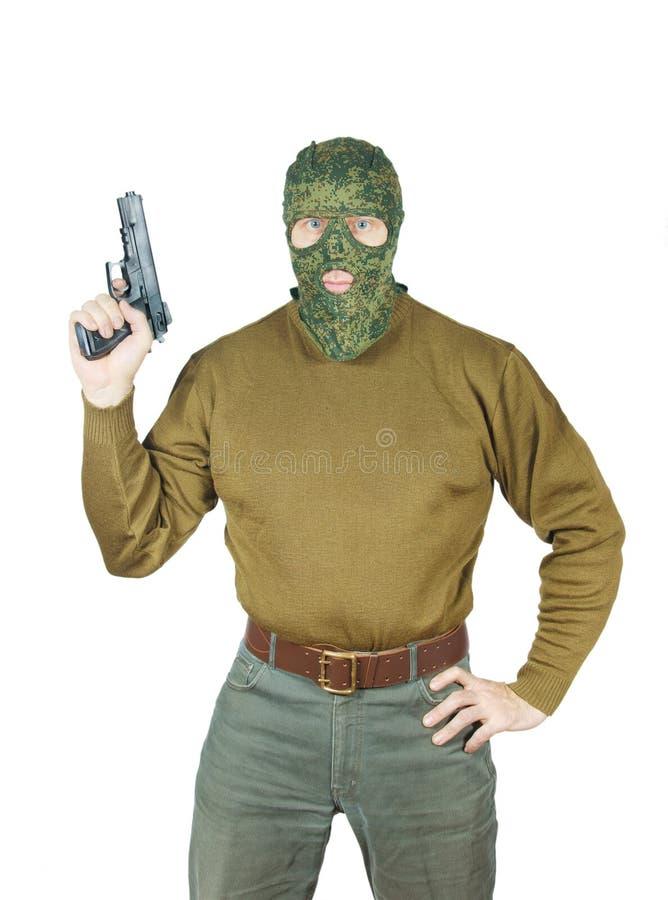Το ισχυρό άτομο που φορά τη μάσκα κάλυψης κρατά ένα πυροβόλο όπλο στοκ φωτογραφία με δικαίωμα ελεύθερης χρήσης