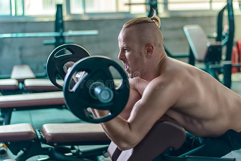 Το ισχυρό αθλητικό άτομο κάνει την άσκηση με τις μπούκλες ιεροκηρύκων στοκ φωτογραφία