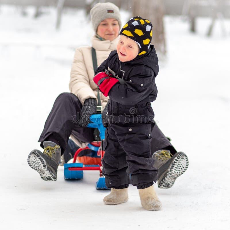 Το ισχυρό μικρό παιδί φέρνει τη μητέρα της σε ένα έλκηθρο στοκ φωτογραφία με δικαίωμα ελεύθερης χρήσης