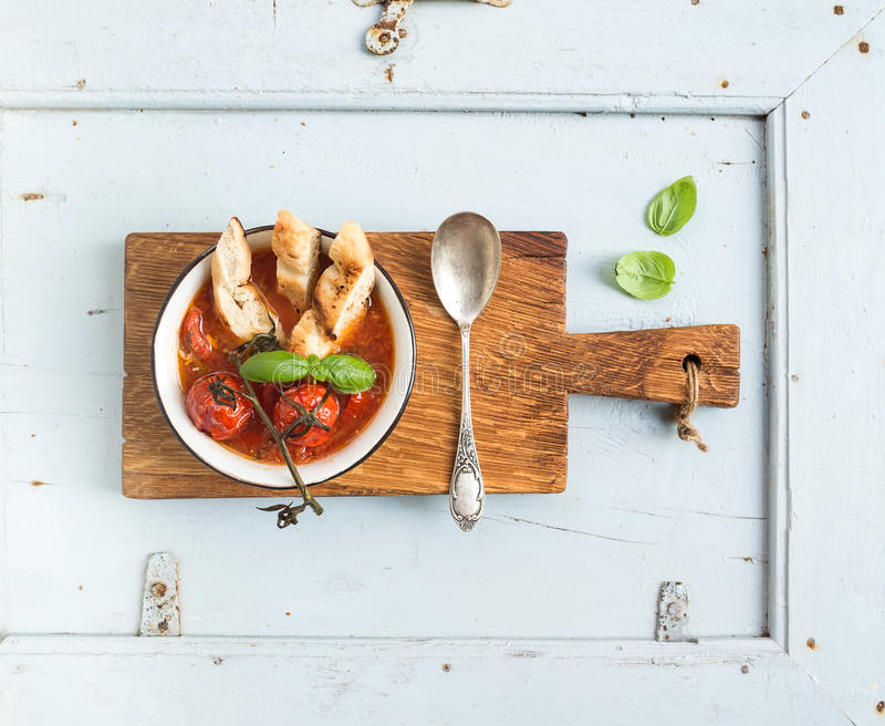 Το ιταλικό Al Pomodoro Pappa σούπας ντοματών, σκόρδου και βασιλικού στο μέταλλο κυλά με το ψωμί στον αγροτικό ξύλινο πίνακα πέρα  στοκ εικόνα με δικαίωμα ελεύθερης χρήσης