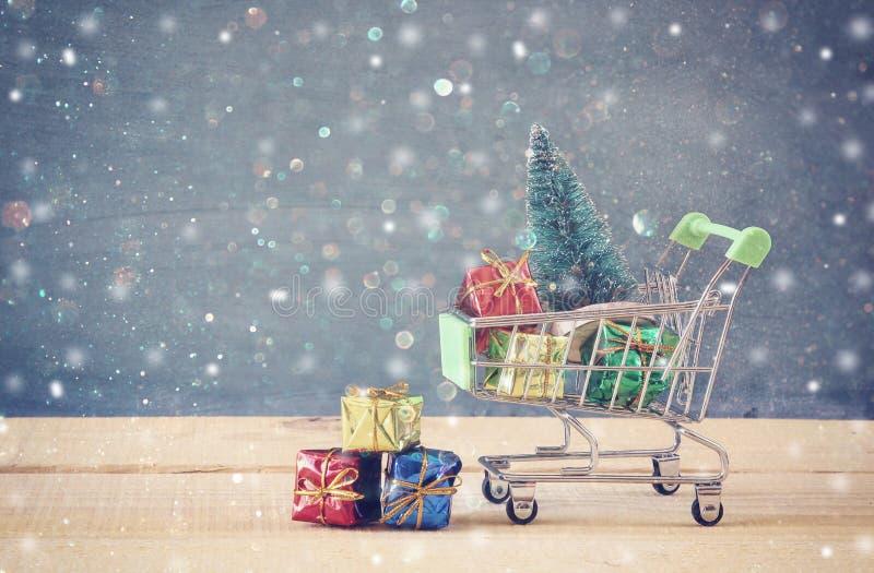 Το κάρρο αγορών με το χριστουγεννιάτικο δέντρο και παρουσιάζει στοκ εικόνες