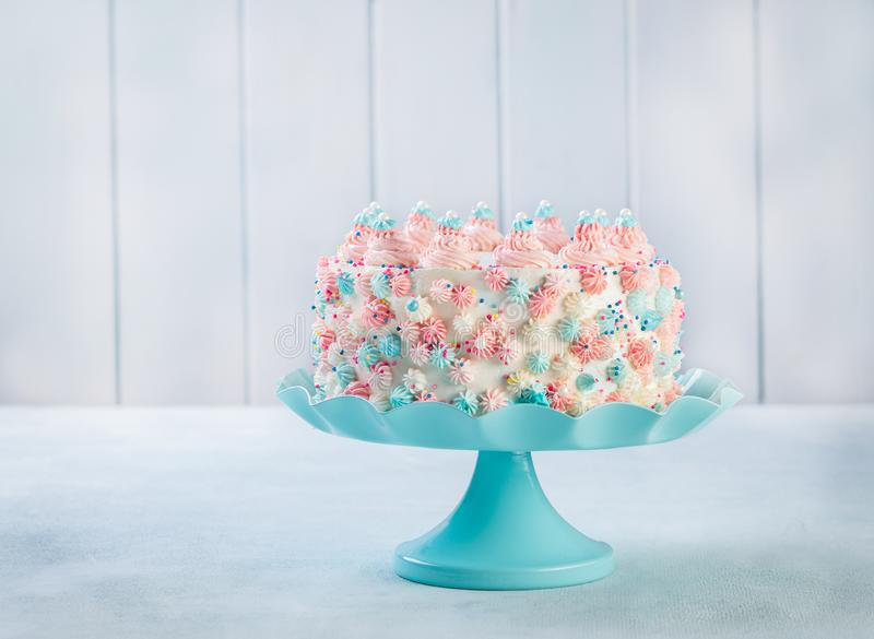 Το κέικ γενεθλίων βανίλιας buttercream με ζωηρόχρωμο ψεκάζει πέρα από ένα ουδέτερο υπόβαθρο στοκ εικόνα