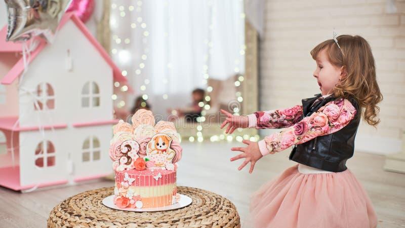 Το κέικ γενεθλίων για 3 έτη διακόσμησε με τις πεταλούδες, το γατάκι μελοψωμάτων με την τήξη και τον αριθμό τρία μαρέγκα χλωμή - ρ στοκ φωτογραφία με δικαίωμα ελεύθερης χρήσης