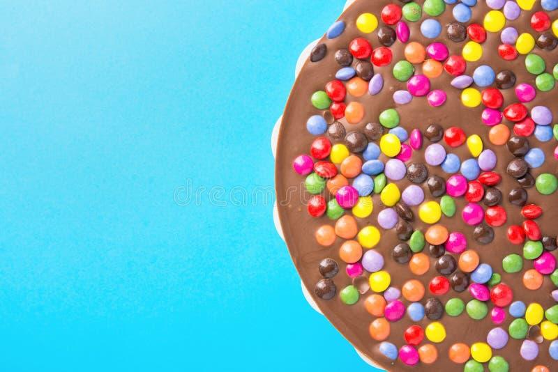 Το κέικ γενεθλίων σοκολάτας γάλακτος με την πολύχρωμη βερνικωμένη καραμέλα ψεκάζει Εύθυμη διάθεση διασκέδασης παιδιών εορτασμού κ στοκ εικόνες με δικαίωμα ελεύθερης χρήσης