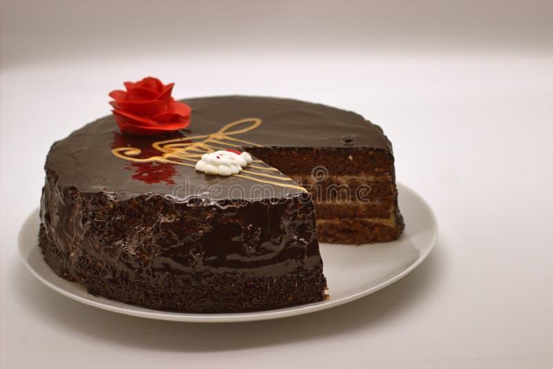 Κέικ σοκολάτας σε ένα άσπρο υπόβαθρο Εικόνα άνωθεν Το κέικ είναι διακοσμημένο με ένα κόκκινο λουλούδι της κρέμας στοκ εικόνα με δικαίωμα ελεύθερης χρήσης