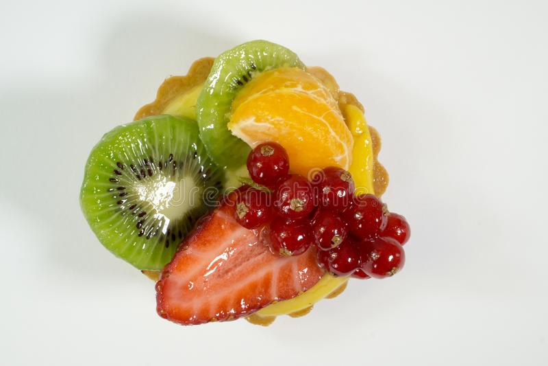 Το κέικ με τα φρέσκα βιο φρούτα, πορτοκάλι, ακτινίδιο, κόκκινη σταφίδα, φράουλα, άποψη φωτογραφιών από το τοπ, άσπρο υπόβαθρο, απ στοκ εικόνα