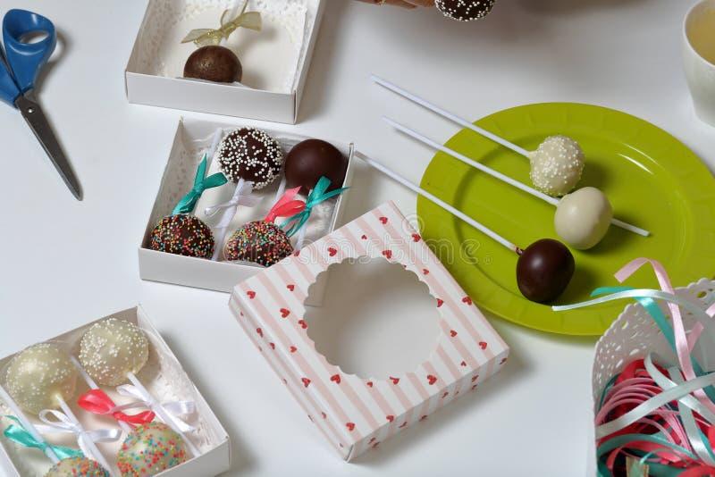Το κέικ σκάει διακοσμημένος με ένα τόξο της πλεξούδας, που συσκευάζεται σε ένα κιβώτιο δώρων Άλλα γλυκά είναι στενά κοντά στο πιά στοκ εικόνα