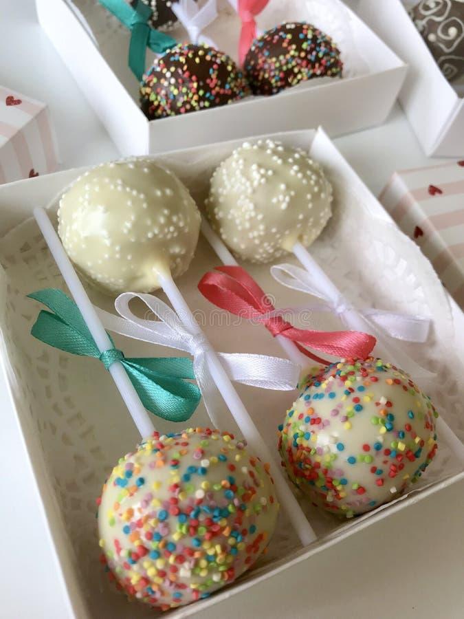 Το κέικ σκάει διακοσμημένος με ένα τόξο της πλεξούδας, που συσκευάζεται σε ένα κιβώτιο δώρων Στην επιφάνεια που καλύπτεται με το  στοκ φωτογραφίες