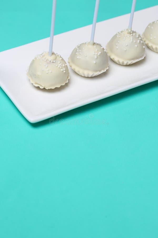 Το κέικ σκάει στο άσπρο λούστρο σοκολάτας Στάση κάθετα σε μια στάση στοκ εικόνα