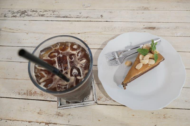 Το κέικ σοκολάτας με την καραμέλα στην κορυφή με τα καρύδια εξυπηρετεί μαζί με το μαύρο καφέ πάγου στοκ εικόνες