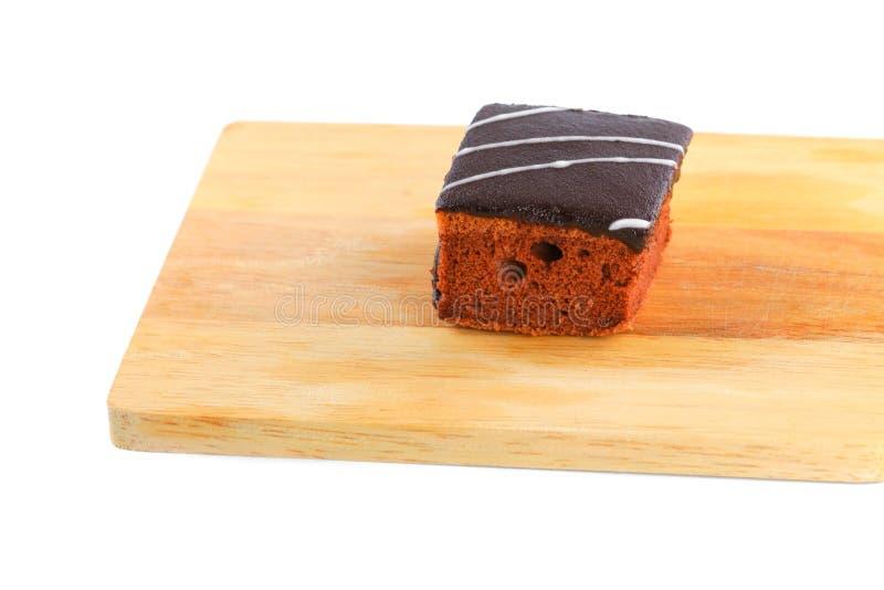 Το κέικ σοκολάτας χύνει την κρέμα στον τέμνοντα πίνακα με το άσπρο υπόβαθρο στοκ φωτογραφία με δικαίωμα ελεύθερης χρήσης