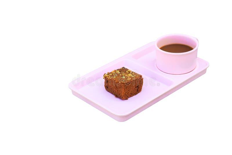 Το κέικ σοκολάτας ψεκάζει με τα καρύδια και το φλυτζάνι καφέ στο ρόδινο πιατάκι απομονωμένος στο άσπρο υπόβαθρο στοκ φωτογραφία με δικαίωμα ελεύθερης χρήσης