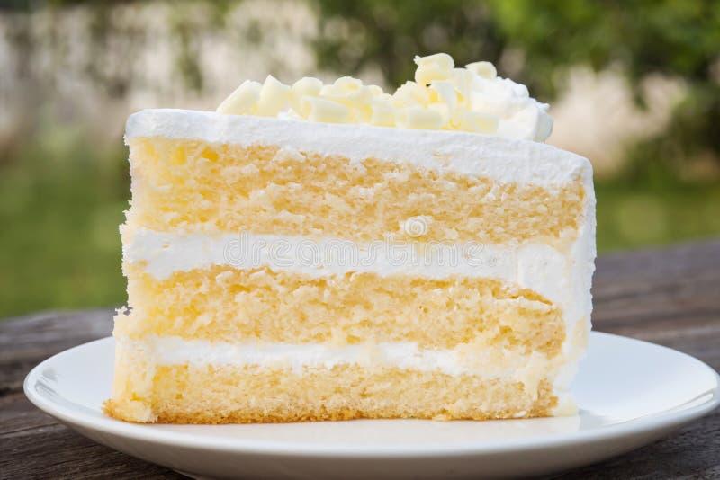 Το κέικ σφουγγαριών βανίλιας με την κρέμα και η άσπρη σοκολάτα διακοσμούν Sli στοκ εικόνα με δικαίωμα ελεύθερης χρήσης