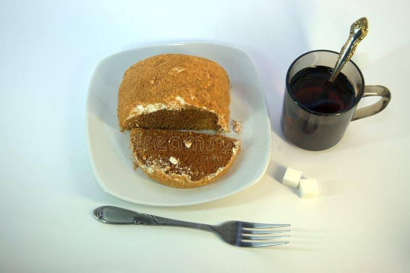 Το κέικ σφουγγαριών σοκολάτας με ψεκάζει σε ένα κεραμικό πιάτο και ένα δίκρανο εδώ κοντά, μια κούπα του καυτού τσαγιού με ψεύτικο στοκ εικόνες με δικαίωμα ελεύθερης χρήσης
