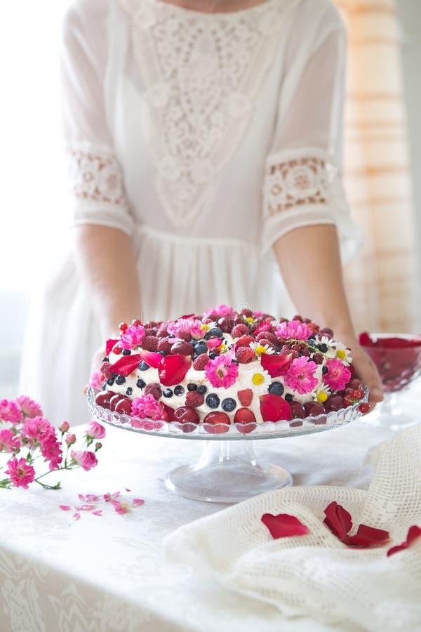 Το κέικ φρούτων μούρων, σπιτικό κέικ μπισκότων με την κρέμα, στα χέρια γυναικών ενάντια του ελαφριού καλοκαιριού ανθίζει το υπόβα στοκ εικόνα με δικαίωμα ελεύθερης χρήσης