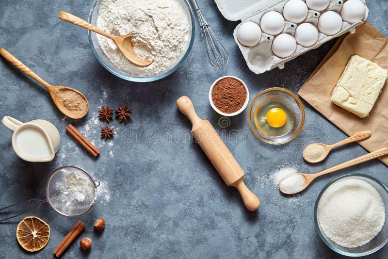 Το κέικ ψησίματος διαδικασίας στην κουζίνα - αυγά συστατικών συνταγής ζύμης, αλεύρι, γάλα, βούτυρο, ζάχαρη στον πίνακα άνωθεν στοκ εικόνα με δικαίωμα ελεύθερης χρήσης