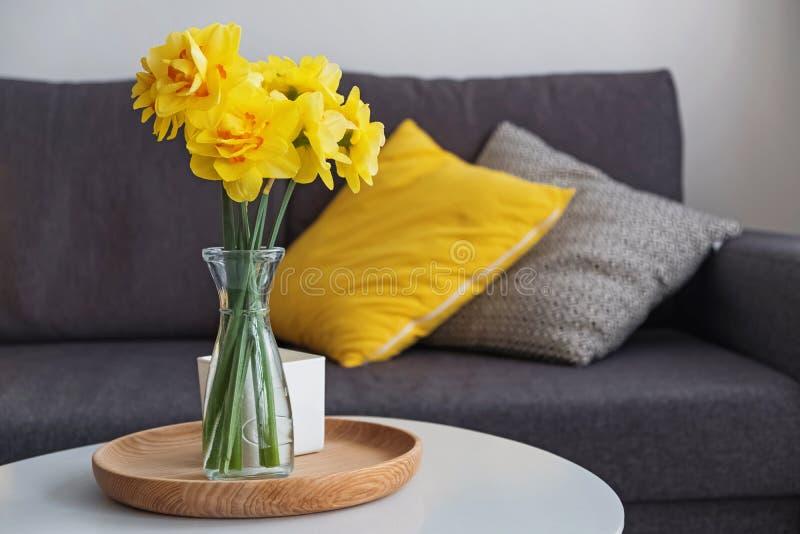 Το κίτρινο ελατήριο ανθίζει σε ένα βάζο που στέκεται στο καθιστικό στον πίνακα coffe στοκ φωτογραφίες