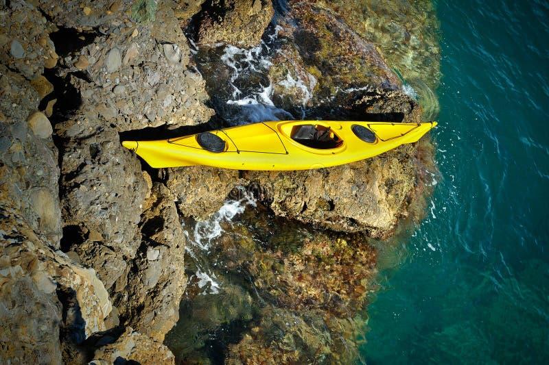 Το κίτρινο καγιάκ θάλασσας τα δύσκολα ορμητικά σημεία ποταμού στοκ φωτογραφία