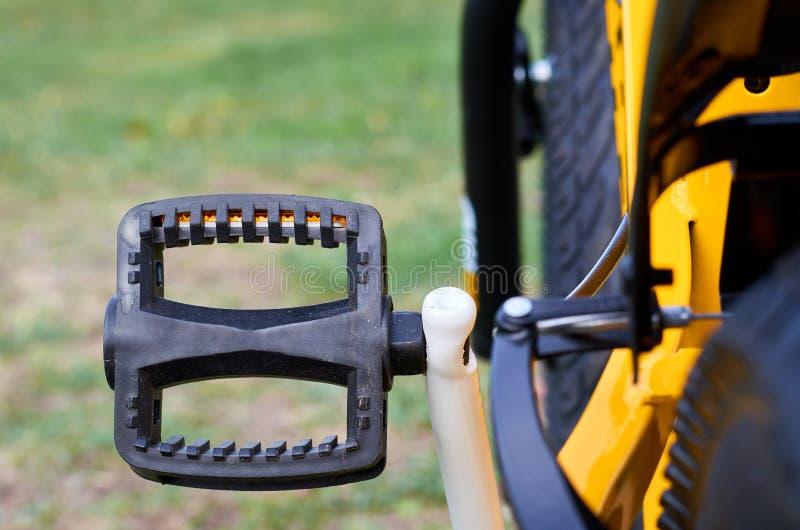 Το κίτρινο ποδήλατο παιδιών στο πάρκο, κλείνει επάνω τα μέρη, πεντάλι στοκ εικόνες με δικαίωμα ελεύθερης χρήσης