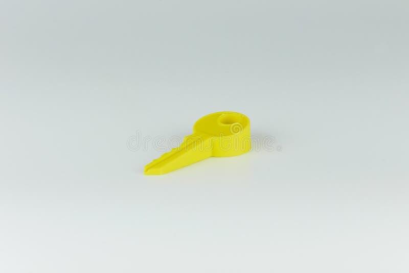 Το κίτρινο πώμα πορτών μορφής κλειδιών χρώματος απομονώνει στο γκρίζο υπόβαθρο στοκ εικόνα