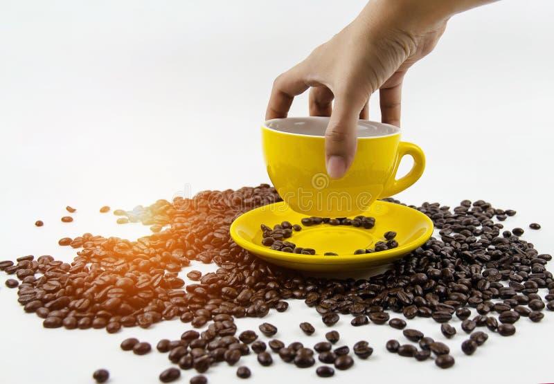 Το κίτρινο φλυτζάνι καφέ κρατούσε από το ανθρώπινο χέρι, βάζοντας το φλυτζάνι στο κίτρινο πιάτο, αφθονία των φασολιών καφέ στο υπ στοκ εικόνες