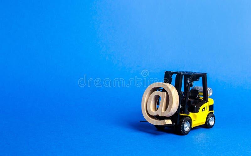 Το κίτρινο Forklift φορτηγό φέρνει το σύμβολο ηλεκτρονικού ταχυδρομείου εμπορικό Ένταξη της βιομηχανίας στις τεχνολογίες δικτύων  στοκ φωτογραφία με δικαίωμα ελεύθερης χρήσης