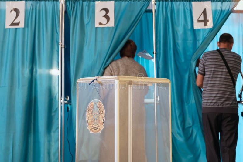Το Καζακστάν, Qazaqstan, στις 9 Ιουνίου 2019, οι εκλογές, η ψηφοφορία, ο άνδρας Α και μια γυναίκα μπαίνουν σε έναν θάλαμο στο δωμ στοκ εικόνες
