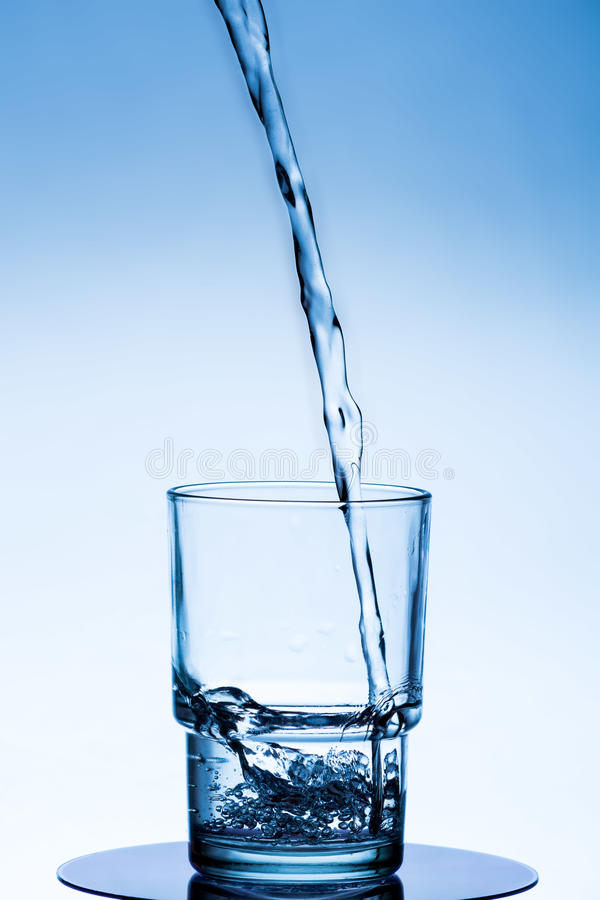 Το καθαρό νερό χύνεται σε μια κούπα γυαλιού σε ένα άσπρος-μπλε υπόβαθρο στοκ φωτογραφία