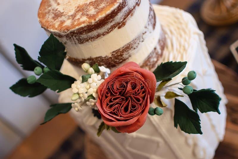 Το καθιερώνον τη μόδα γαμήλιο κέικ με εδώδιμο αυξήθηκε floral ρύθμιση Το κέικ χαρακτηρίζει μια γυμνή τοπ σειρά με μια πλεκτή κατώ στοκ φωτογραφίες με δικαίωμα ελεύθερης χρήσης