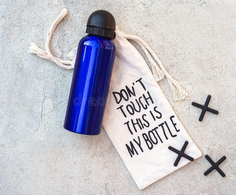 Το καθορισμένες μπλε μπουκάλι νερό έφηβη ή αγοριών και η τσάντα ιστού με την εγγραφή φορούν την αφή ` τ που αυτό είναι το μπουκάλ στοκ εικόνες
