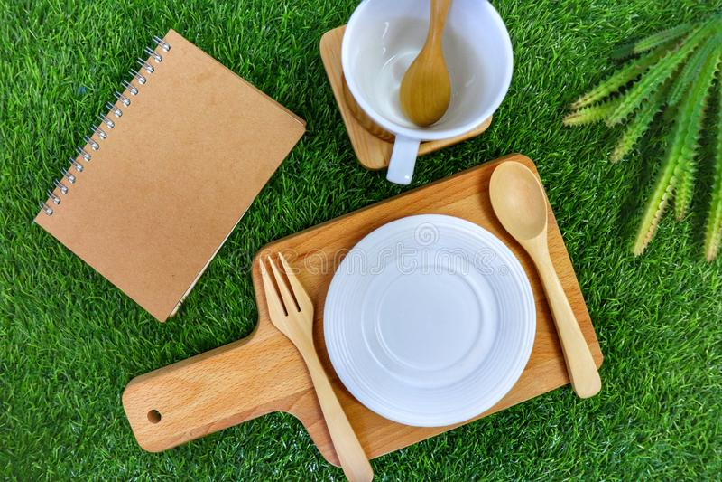 Το καθορισμένο flatware ύφος αγροτικό έχει το κουτάλι, το δίκρανο, το κενά πιάτο και το φλυτζάνι στο πράσινο υπόβαθρο χλόης στοκ φωτογραφίες με δικαίωμα ελεύθερης χρήσης