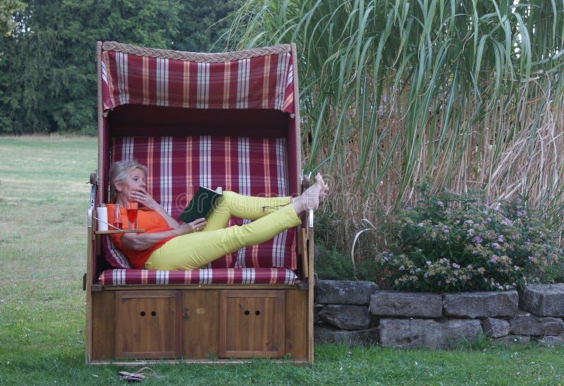 Το καινούργιο βιβλίο, ένα δροσερό ποτό και sunscreen είναι όλο το μέρος μιας χαλαρώνοντας ημέρας η ψάθινη καρέκλα παραλιών στοκ εικόνα
