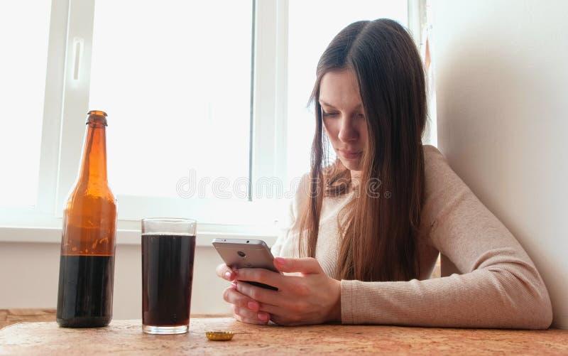 Το και ανήσυχο νέο κορίτσι που δακτυλογραφεί ένα μήνυμα σε ένα κινητό τηλέφωνο και πίνει την μπύρα στοκ εικόνες με δικαίωμα ελεύθερης χρήσης