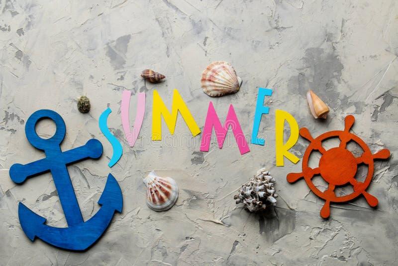 Το καλοκαίρι λέξης από το έγγραφο με τις πολύχρωμα επιστολές και τα εξαρτήματα θάλασσας, κοχύλια σε ένα ελαφρύ συγκεκριμένο υπόβα στοκ φωτογραφίες