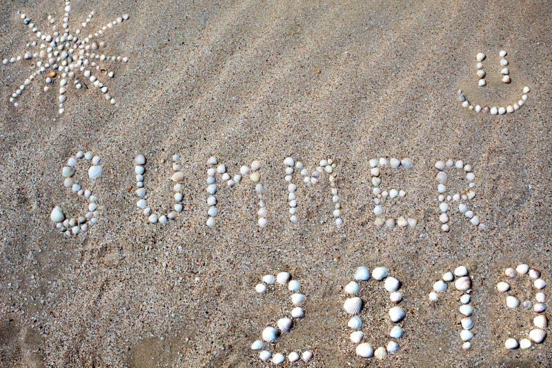 Το καλοκαίρι λέξης, ο αριθμός του ήλιου και το χαμόγελο, το σχήμα το 2019 σχεδιάζεται στην άμμο με τα κοχύλια στοκ εικόνες