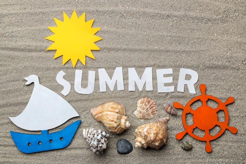 Το καλοκαίρι λέξης των άσπρων επιστολών εγγράφου και των εξαρτημάτων καλοκαιριού και θάλασσας στην άμμο θάλασσας o r χαλάρωση r στοκ φωτογραφία με δικαίωμα ελεύθερης χρήσης