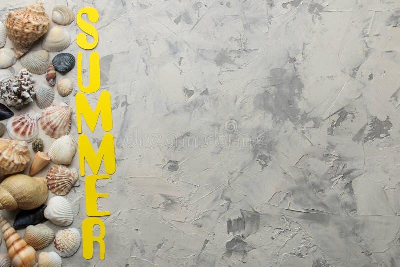 Το καλοκαίρι λέξης των κίτρινων επιστολών εγγράφου και των εξαρτημάτων θάλασσας, κοχύλια σε ένα ελαφρύ συγκεκριμένο υπόβαθρο o r  στοκ εικόνες