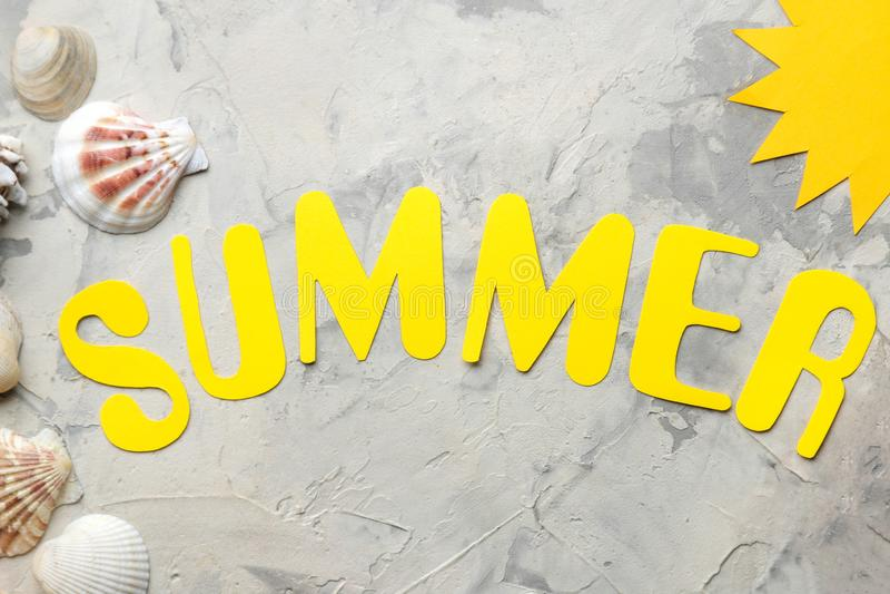 Το καλοκαίρι λέξης των κίτρινων επιστολών εγγράφου και των εξαρτημάτων θάλασσας, κοχύλια σε ένα ελαφρύ συγκεκριμένο υπόβαθρο o r  στοκ εικόνα
