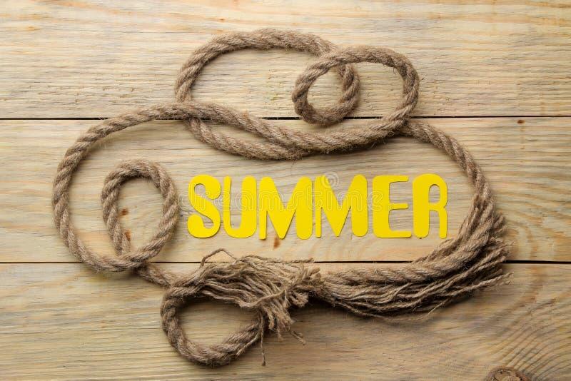 Το καλοκαίρι λέξης φιαγμένο από κίτρινα επιστολές εγγράφου και σχοινί θάλασσας σε ένα φυσικό ξύλινο υπόβαθρο o r χαλάρωση r στοκ φωτογραφίες με δικαίωμα ελεύθερης χρήσης