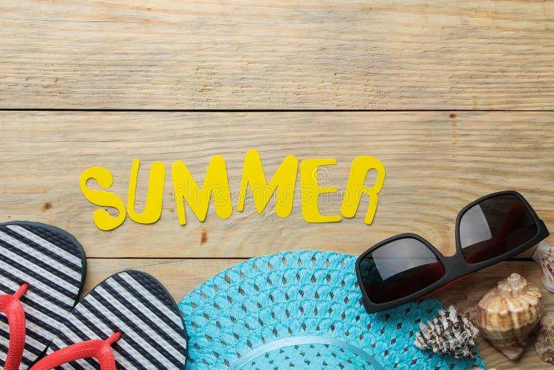 Το καλοκαίρι λέξης φιαγμένο από κίτρινες επιστολές εγγράφου και καλοκαίρι, εξαρτήματα παραλιών σε ένα φυσικό ξύλινο υπόβαθρο o r  στοκ φωτογραφία με δικαίωμα ελεύθερης χρήσης