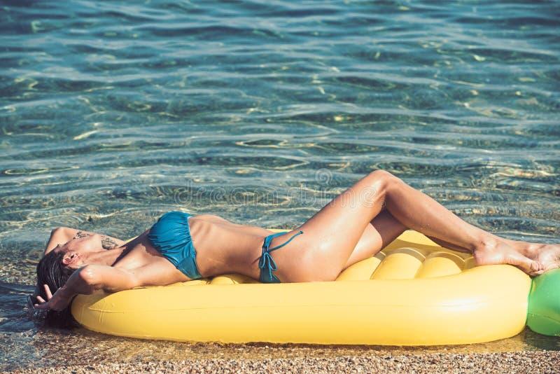 Το καλοκαίρι χαλαρώνει της προκλητικής γυναίκας στο κίτρινο στρώμα στοκ φωτογραφίες