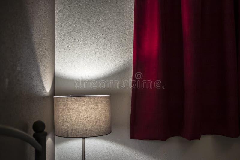 Το καλυμμένο φως από το λαμπτήρα πατωμάτων δημιουργεί μια χαλάρωση, οικεία ατμόσφαιρα στην κρεβατοκάμαρα με τις παχιές κόκκινες κ στοκ εικόνα με δικαίωμα ελεύθερης χρήσης