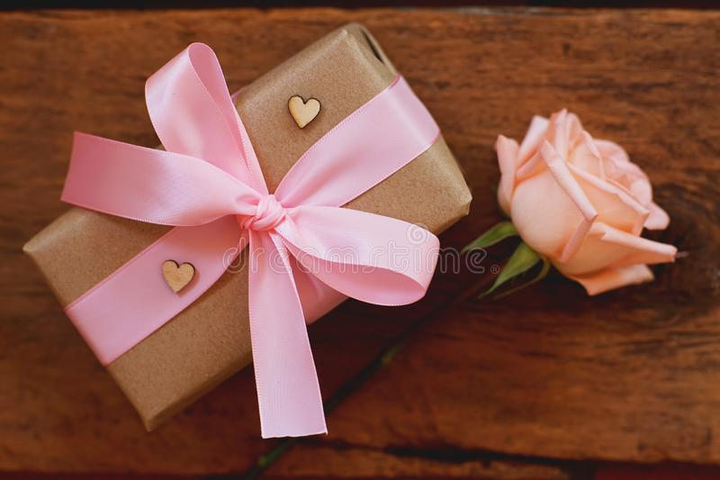 Το καλό μαλακό πορτοκαλί ρόδινο χρώμα αυξήθηκε δεμένος από τη ρόδινη κορδέλλα και το καφετί κιβώτιο δώρων στο ξύλινο επιτραπέζιο  στοκ φωτογραφία
